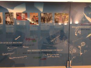 Auf einer Ausstellungswand in der DenkStätte Weiße Rose beantworten BesucherInnen die Frage, was Widerstand für sie bedeutet, u.a. mit den Begriffen 'Menschlichkeit', 'Gerechtigkeit', 'Gleichberechtigung' und 'Freiheit'